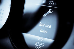 Service now. Detail with a warning icon on the dashboard of a car reading Service Now Stock Photo