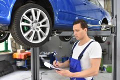 Service och kontroll av en bil i ett seminarium - mekanikern kontrollerar royaltyfri foto