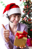 Service operator on Christmas back showing ok sign with present Royalty Free Stock Images