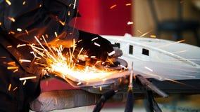Service professionnel de voiture - la construction de meulage en métal de travailleur avec une scie de circulaire, se ferment  photographie stock