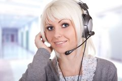 Service provider. The young girl in ear-phones with a microphone, a communications service provider Stock Image