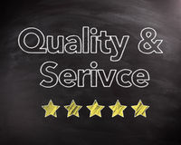 Service and Quality Texts on Chalkboard with Stars. Conceptual Service and Quality Texts on Black Chalkboard with Five Yellow Stars, Captured in Close up Stock Photography