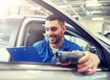 Mechanic man with diagnostic scanner at car shop stock images