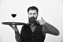 Service and restaurant catering concept. Man and mustache holds alcohol on white background. Waiter points at tray and. Glass of red wine. Barman with serious Stock Photography