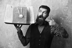 Service and shopping concept. Waiter with silver packages on tray. Man with beard holds shopping bags on beige wall. Background. Businessman with surprised face royalty free stock images