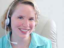 Service With A Smile. Young woman with headset Stock Images