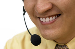 Service With A Smile. Close up of a man smiling as he helps out a customer on the line through a headset Stock Photos