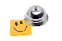 Service With A Smile On White. Reception Service Bell With Happy Face Note, In A Depiction Of Service With A Smile On White Background Stock Image