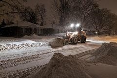 Service snow plowing truck cleaning residential street during heavy snowstorm, Toronto, Ontario, Canada. stock photos