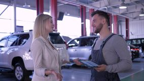 Service station, happy client girl and mechanic talking about car maintenance at auto repair shop stock video footage