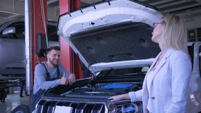 Service station, portrait of happy lady consumer car owner during working process mechanic man repairs vehicle with open. Hood at workshop stock footage