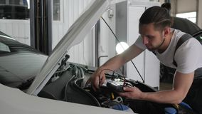 Service station, professional mechanician male stands near open hood checks wiring automobile system, engine review stock video