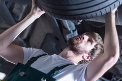 Service station worker checking tire Stock Image