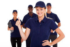 Service thumb up. Technical service women thumb up with team in background Stock Photography