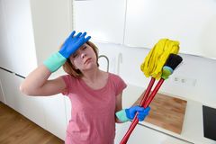 Service woman at home kitchen in gloves carrying cleaning broom and mop frustrated Stock Photos