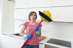 Service woman at home kitchen in gloves carrying cleaning broom and mop frustrated Stock Photography