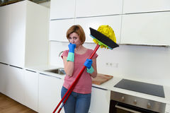 Service woman at home kitchen in gloves carrying cleaning broom and mop frustrated Royalty Free Stock Image