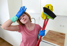 Service woman at home kitchen in gloves carrying cleaning broom and mop frustrated Royalty Free Stock Images