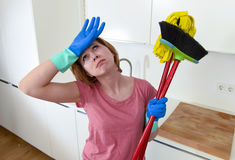 Service woman at home kitchen in gloves carrying cleaning broom and mop frustrated Stock Images
