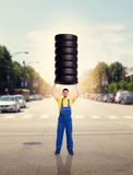 Service worker holds pile of tires over head. Tyre service worker in uniform holds pile of tires over head. Repairman, wheel mounting Royalty Free Stock Photo