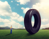 Service worker holds pile of tires over head. Service worker in uniform against giant tire. Repairman, wheel mounting. Tyre serviceman Stock Images