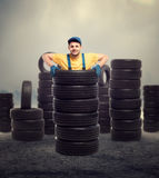 Service worker inside pile of tires, tyre industry. Service worker is standing inside a pile of tires, tyre industry, repairman, wheel mounting Stock Image