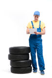 Service worker with notebook against pile of tires. Tyre service worker in uniform with notebook against pile of tires, white background, repairman, wheel Royalty Free Stock Photos