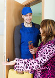 Service worker in uniform came to housewife Royalty Free Stock Photography