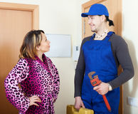 Service worker in uniform came to housewife. Happy service worker in uniform came to housewife Stock Image