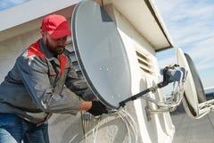 Servicearbetare som installerar och passar maträtten för satellit- antenn för kabel-TV arkivfoto