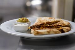 A serviced quesadilla with sauces royalty free stock images