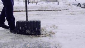 Serviceföretaget gör ren gården av huset och trottoarerna från snön och isen Två män i likformig arbetar, lager videofilmer