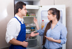 Serviceman asking housewife of technical problems with fridge Royalty Free Stock Photo