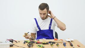 Serviceman in blue work suit sits for the work table.  Royalty Free Stock Photos