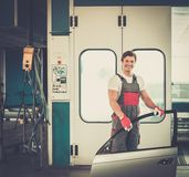 Serviceman in a car workshop. Cheerful serviceman with car door near paint booth in a car body workshop stock images