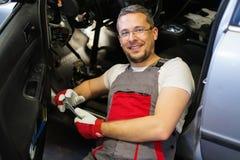 Serviceman in car workshop Stock Photo