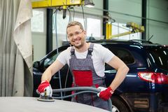 Serviceman in car workshop Royalty Free Stock Image