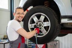 Serviceman in car workshop. Cheerful serviceman unscrewing wheel in car workshop royalty free stock photos