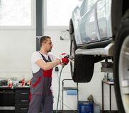 Serviceman in car workshop Stock Photos