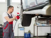Serviceman in car workshop Royalty Free Stock Images