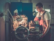 Serviceman in car workshop Stock Images