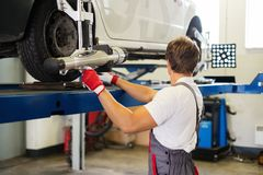 Serviceman in a car workshop. Young serviceman checking wheel alignment  in a car workshop Stock Photo