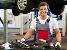 Serviceman in car workshop Stock Images