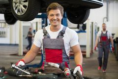 Serviceman in car workshop Stock Photography