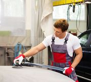 Serviceman in car workshop Stock Photo