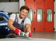 Serviceman in a car workshop Stock Image