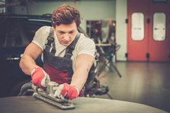 Serviceman in a car workshop. Young serviceman performing grinding with machine on a car bonnet in a workshop Royalty Free Stock Photos