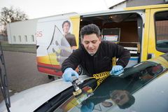Serviceman from carglass. ENSCHEDE, THE NETHERLANDS - 21 NOV, 2014: A serviceman from 'carglass' is repairing a crack in the windshield of a car on location stock images