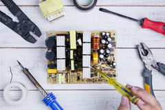 Serviceman check circuit board with electrical tester screwdrive Stock Photography