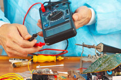 Serviceman checks board of electronic device with a multimeter. In the service workshop Stock Photos